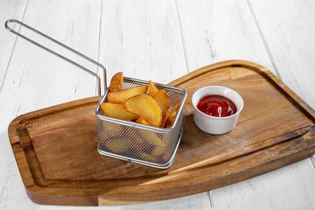 Panier de pommes de terre frites avec du ketchup sur un bureau en bois
