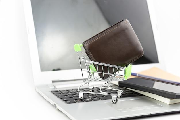 Panier et portefeuille sur fond de cahier et ordinateur portable. achats en ligne, économies d'investissement, achat, concept d'entreprise.