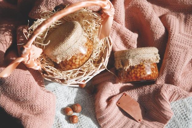 Panier, un pot de pignons de pin au miel, une noisette en coque, un plaid sur la table. nature morte.