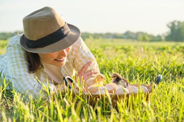 Panier avec des poulets nouveau-nés, femme heureuse au chapeau à la recherche de poussins