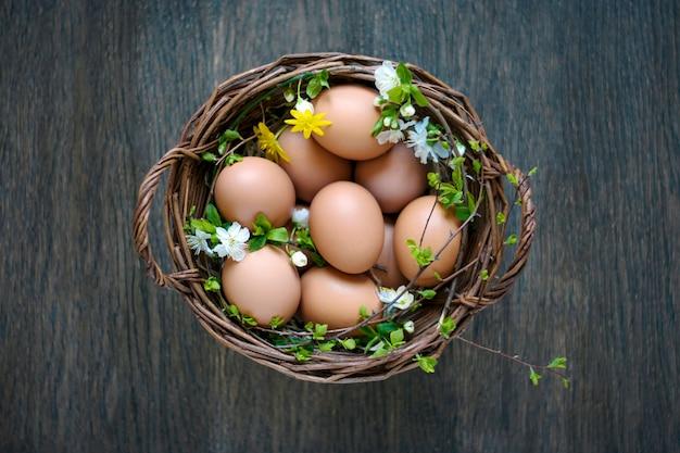 Panier de printemps d'oeufs naturels de pâques sur mur en bois, vue de dessus.