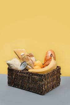 Panier avec des produits alimentaires sur un mur jaune