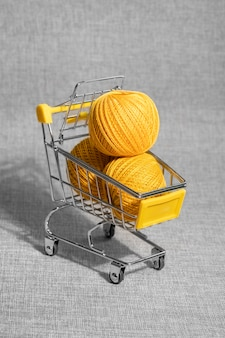 Panier à provisions sur roues. pelotes de fil jaune à tricoter.