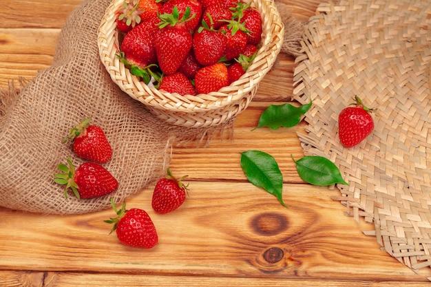 Panier de récolte de fraises sur table en bois se bouchent