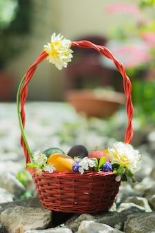 Panier rempli d'oeufs de pâques colorés et décoré de fleurs blanches sur les rochers