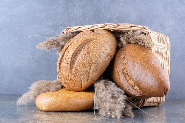 Panier rempli de pains de pain et de tiges d'herbe de plumes sur la surface en marbre