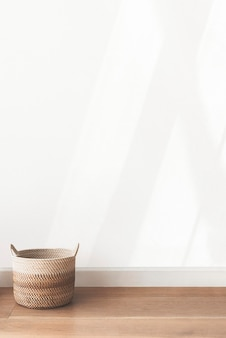 Panier en rotin par un fond de mur blanc
