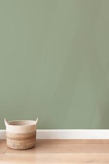 Panier en rotin par un fond de mur vert