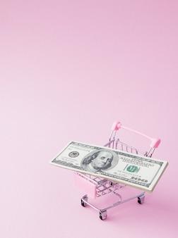 Panier de supermarché plein de billets en dollars américains sur fond rose avec espace de copie. libre échange. marché monétaire. style de minimalisme. chariot de magasin au supermarché. vente, remise