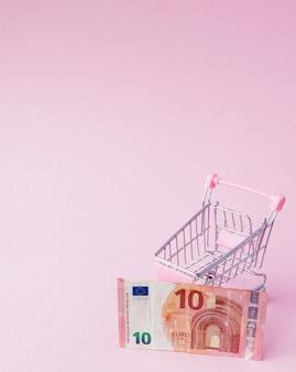 Panier de supermarché plein de billets en euros sur fond rose avec espace de copie. libre échange. marché monétaire. style de minimalisme. chariot de magasin au supermarché. vente, remise