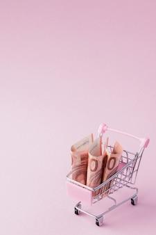 Panier de supermarché plein de billets en euros sur un rose