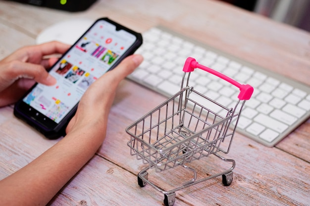 Panier sur table en bois derrière une femme à l'aide d'un smartphone flou shopping en ligne