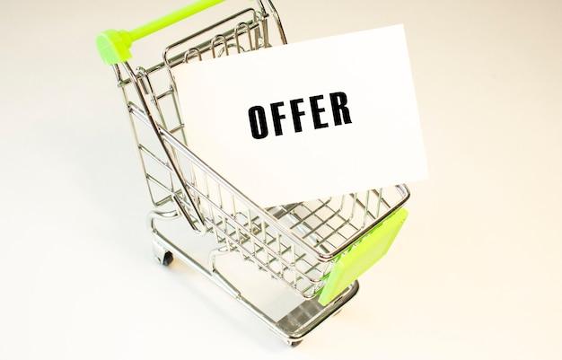 Panier et texte offre sur papier blanc. concept de liste de courses sur fond clair.