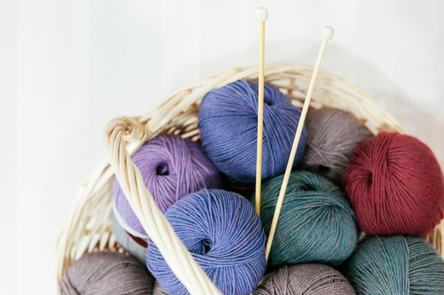 Panier traditionnel avec une variété de bois de fils et d'aiguilles à tricoter