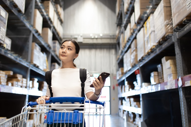 Panier d'utilisation de femme pour l'achat de meubles dans un entrepôt