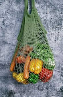 Panier vert plein de légumes sur mur gris
