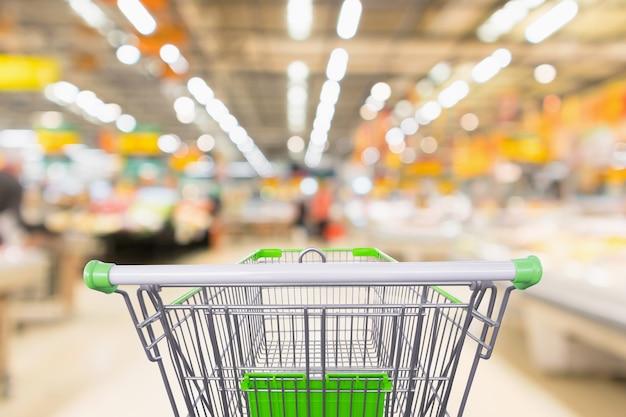 Panier vert vide avec supermarché flou