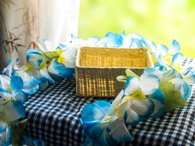 Panier vide et bouquet de fleurs en tissu sur une table près de la fenêtre.