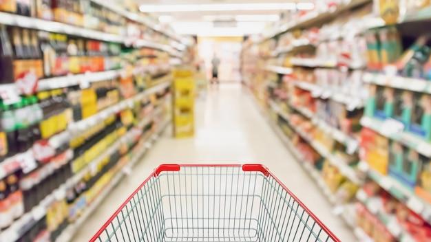 Panier vide avec des étagères de supermarchés allée intérieure flou fond défocalisé