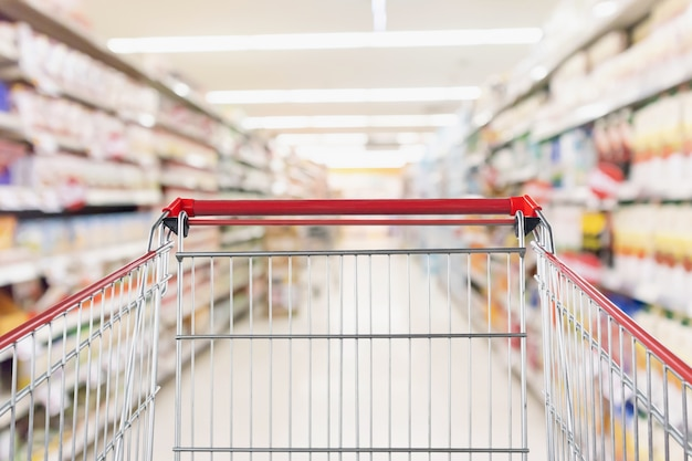 Panier vide avec flou abstrait magasin discount supermarché allée et intérieur des étagères de produits