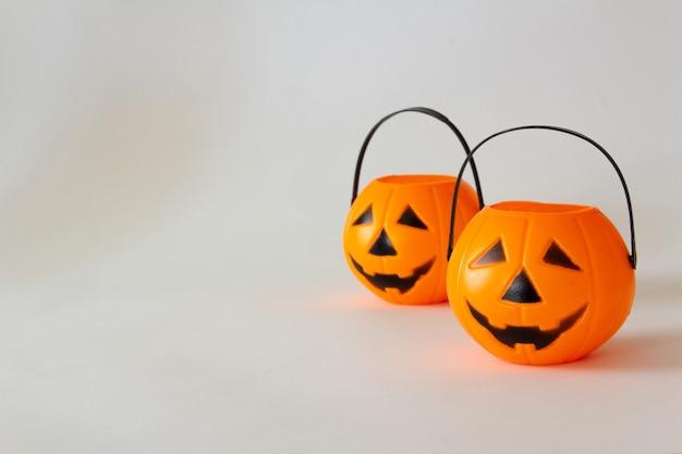 Paniers de bonbons en forme de citrouille lanterne d'halloween sur fond blanc copy space