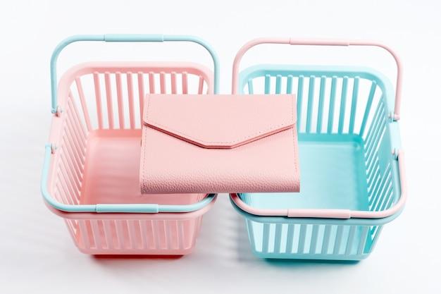 Paniers en plastique colorés avec portefeuille en cuir. paniers de supermarché roses et bleus vides sur fond clair. design créatif, shopping, vendredi noir, remise, publicité, concept de vente.