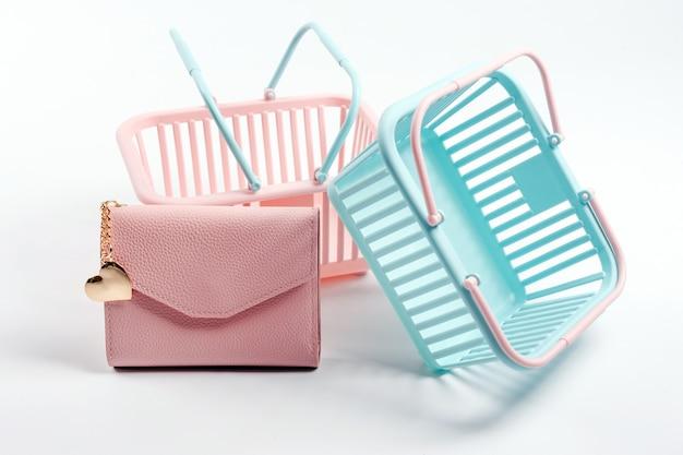Paniers en plastique colorés avec portefeuille en cuir. paniers de supermarché roses et bleus vides sur fond gris clair. design créatif, shopping, vendredi noir, remise, publicité, concept de vente.