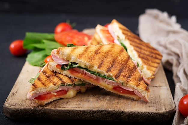 Panini club sandwich au jambon, tomate, fromage et basilic.