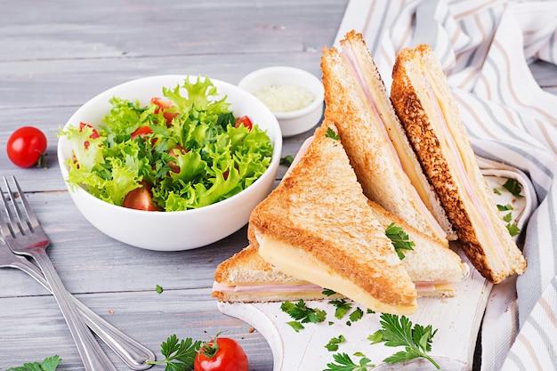 Panini sandwich club avec jambon, fromage et salade. petit déjeuner savoureux