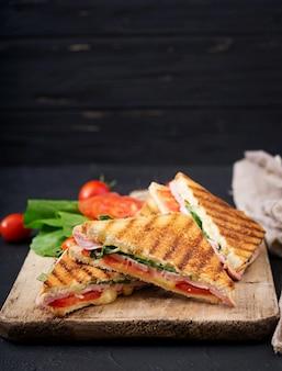 Panini sandwich club avec jambon, tomate, fromage et basilic.