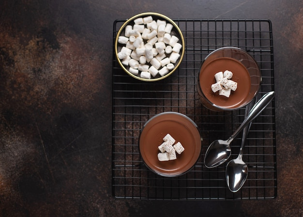 Panna cotta au chocolat avec guimauves surface texturée foncée monochrome marron