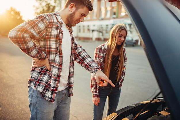 Panne de voiture, homme et femme contre capot ouvert