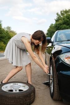 Panne de voiture, jeune femme met le pneu de secours