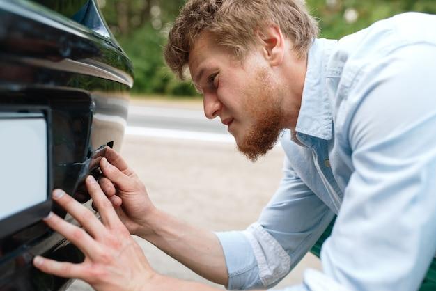 Panne de voiture, jeune homme vissé dans le crochet de remorquage.