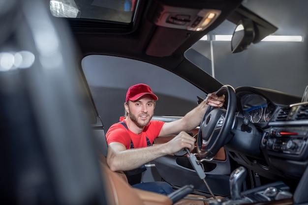 Panne de voiture. mécanicien automobile professionnel satisfait dans la voiture de dépannage des vêtements de travail tout en travaillant dans la cabine tenant le volant