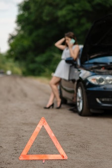 Panne de voiture, panneau d'arrêt d'urgence, femme appelant à l'aide