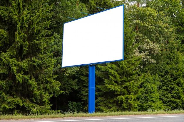 Panneau d'affichage blanc blanc contre la forêt verte le long de la route