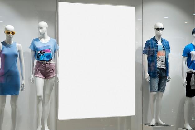 Panneau d'affichage blanc à côté des mannequins