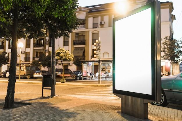 Panneau d'affichage blanc éclairé au bord de la route