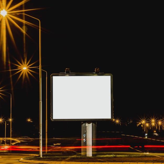 Panneau d'affichage blanc avec feux de circulation la nuit