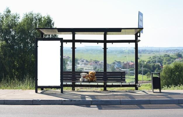 Panneau d'affichage blanc vertical à un arrêt de bus dans une rue de la ville journée ensoleillée d'été ours en peluche à l'arrêt de bus