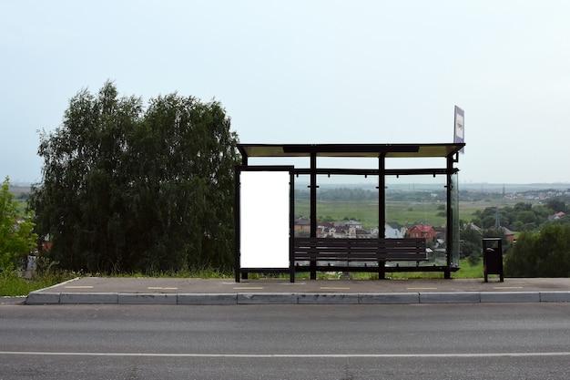Panneau d'affichage blanc vertical à un arrêt de bus sur fond de rue avec bâtiments et route