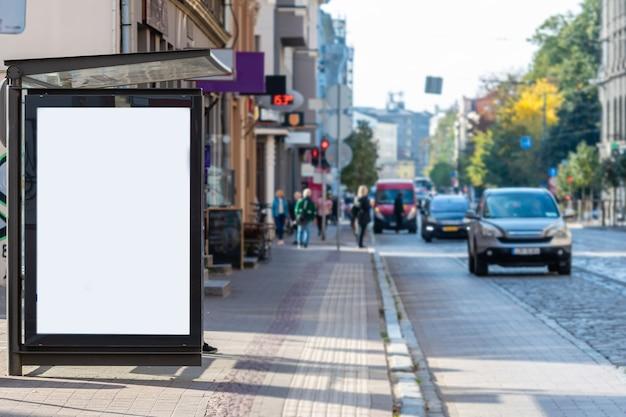 Panneau d'affichage blanc vide vertical à l'arrêt de bus sur la rue de la ville, maquette
