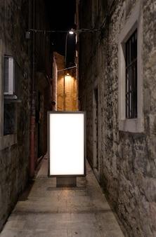 Panneau d'affichage dans la vieille ville au fond de nuit.maquette de panneau publicitaire vide dans la rue