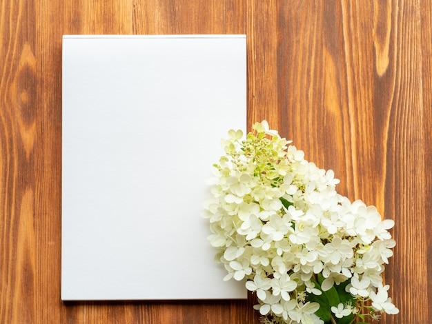 Panneau d'affichage avec une feuille vierge pour les notes et l'hortensia fleur blanche abstrait fond en bois blanc.