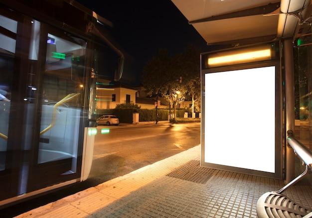 Panneau d'affichage avec lumière dans le centre-ville la nuit avec bus
