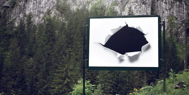 Panneau d'affichage pour affiche publicitaire avec trou de papier déchiré sur fond de forêt verte.