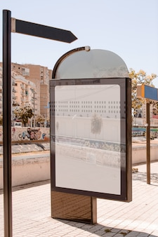 Panneau d'affichage près du poteau indicateur sur le trottoir