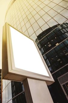 Panneau d'affichage publicitaire vierge devant le bâtiment de l'entreprise. la bannière sur fond de gratte-ciel est réalisée dans un style moderne. architecture du bâtiment dans le quartier de la métropole. espace de copie pour le site