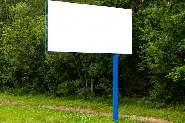 Panneau d'affichage vide blanc contre la forêt verte le long de la route
